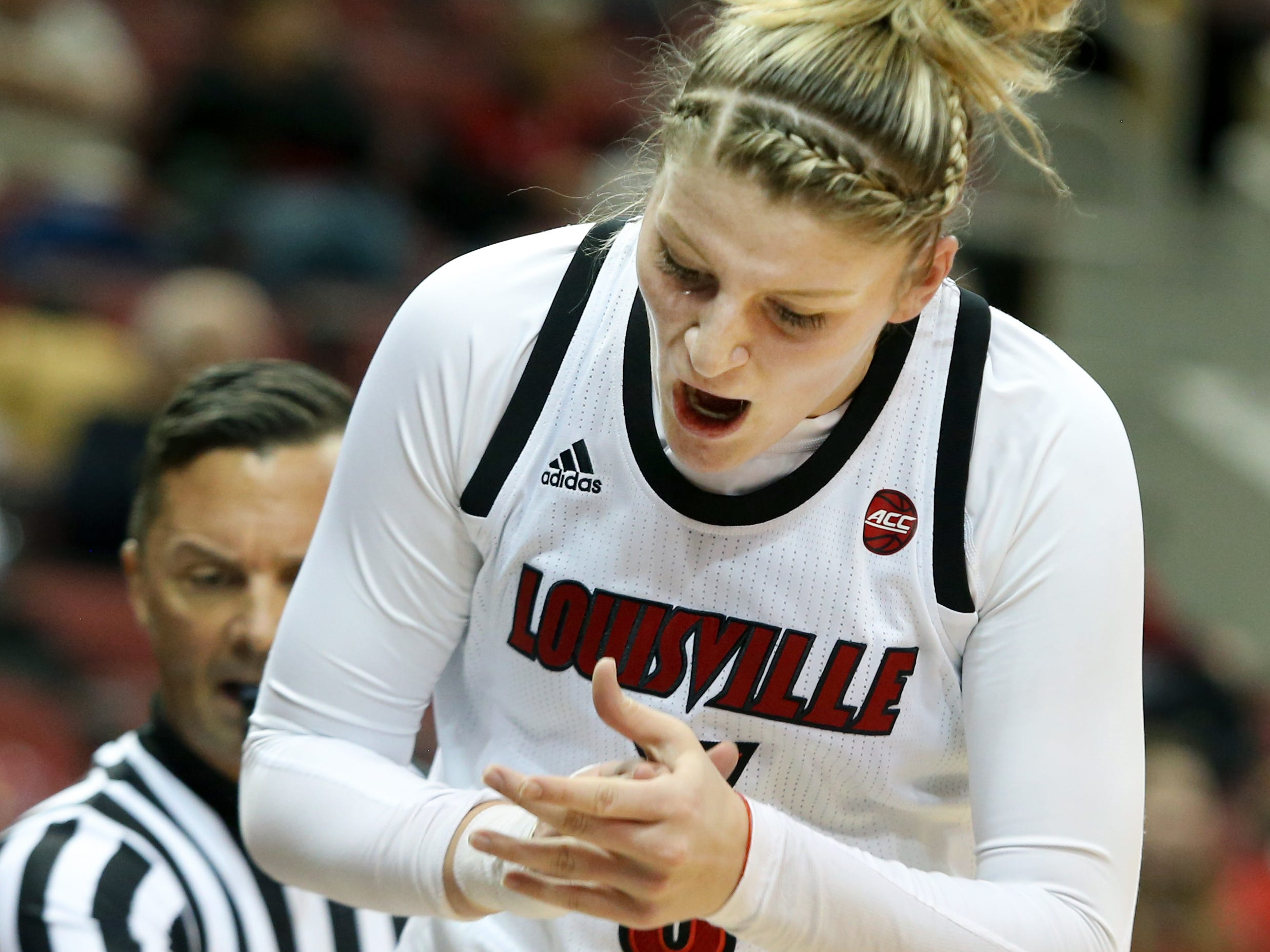 Louisville's Sam Fuehring offers advice to the player on the floor that was guarding her. Dec. 4, 2018