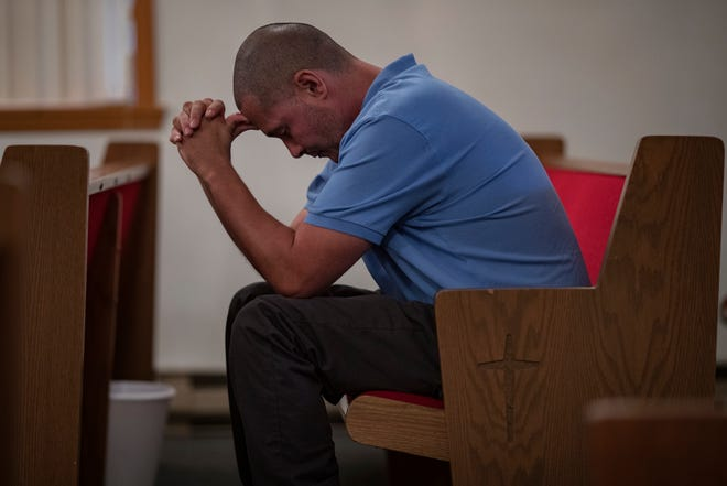 "Austin resident Chris Arevalos sits in the back of a Pentecostal church in prayer on a Sunday evening. Arevalos was once a major narcotics trafficker in the small Indiana town, before getting arrested after a trip to see dealers in Mexico. ""I remember watching all the news about the HIV outbreak while I was in prison,"" Arevalos said. ""It was hard not to feel like I held some responsibility."" Since his release, Arevalos has returned to Austin and has been trying to stay on the straight and narrow. ""It's hard and I see it so much, it just takes one time."" Aug. 12, 2018"