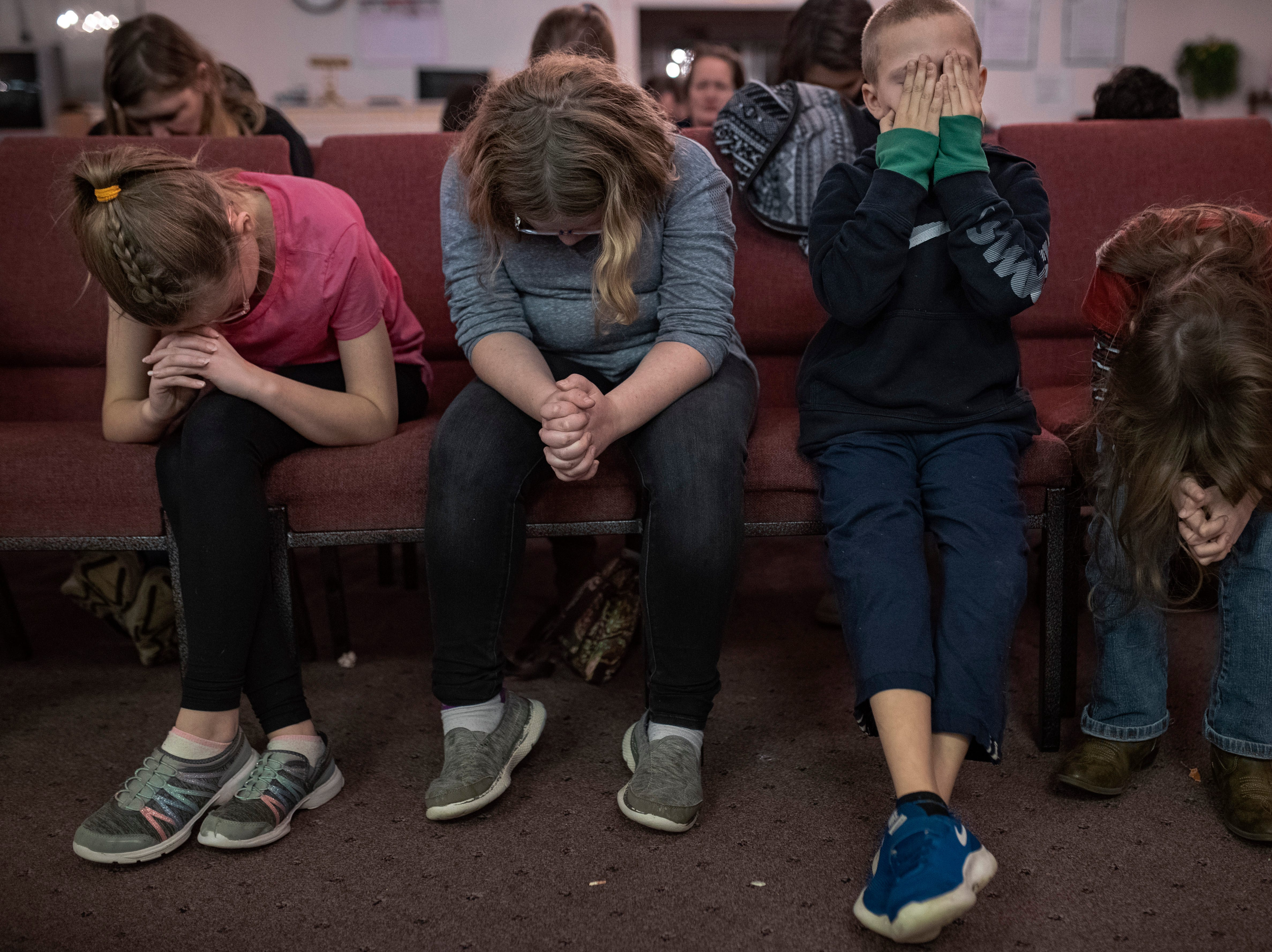 "Children pray at the close of Thursday evening youth programs at Hope To Others Church in Austin's north side. Much of the youth present, typically between age five and ten, prayed for their parents and struggles they may be facing. ""Some kids that are coming start to bring their parents with them,"" co-founder Billy Snowden said. ""We're just trying to end the cycle and create a new one where they can find some hope."" Nov. 29, 2018"