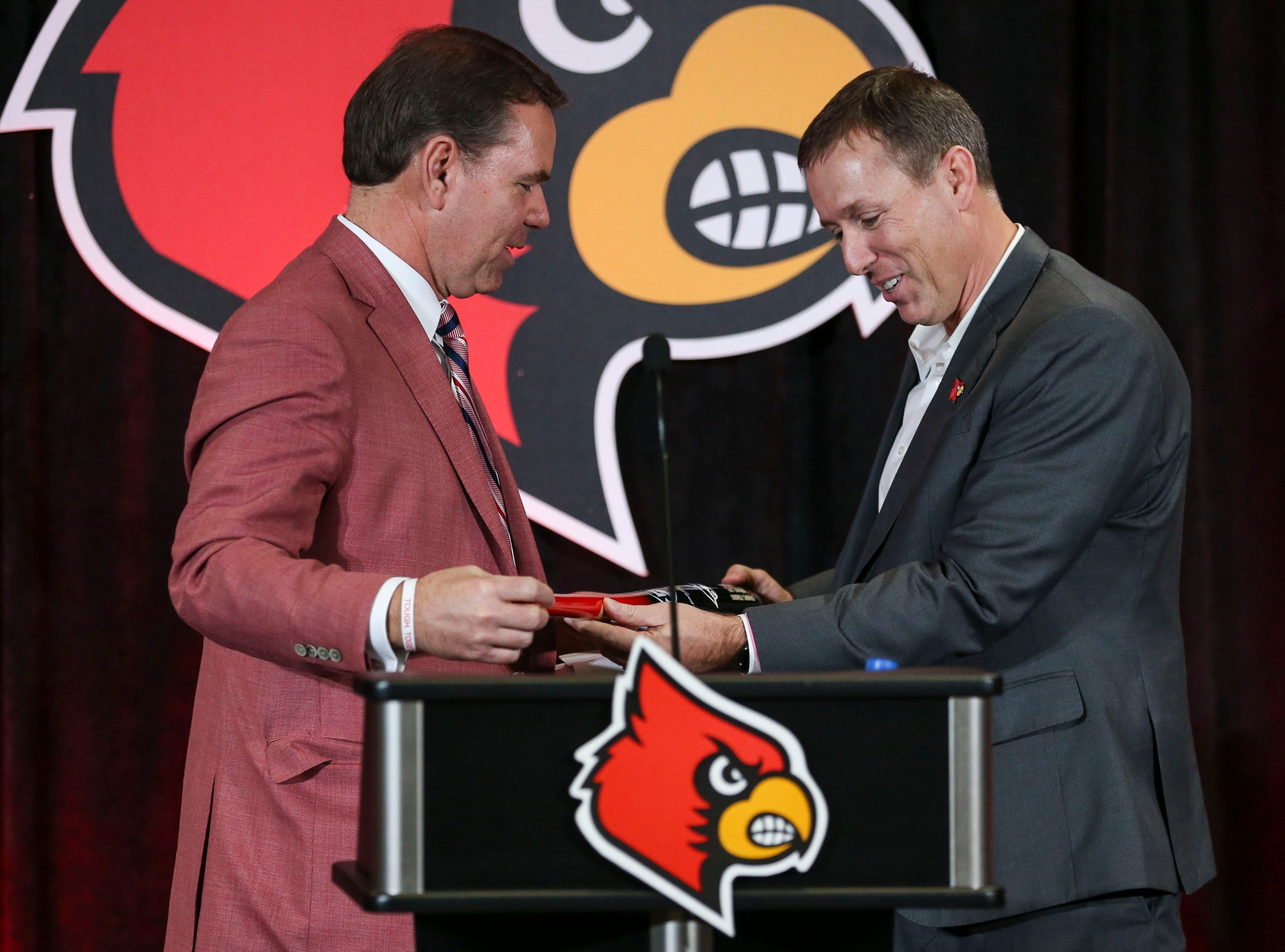 Louisville athletic director Vince Tyra gives new football coach Scott Satterfield a Louisville slugger bat as a welcome present during the new coach's introduction. Satterfield, who coached Appalachian State to one of best FBS records in the past four years, was hired Dec. 4, 2018 to take over the Louisville football program.