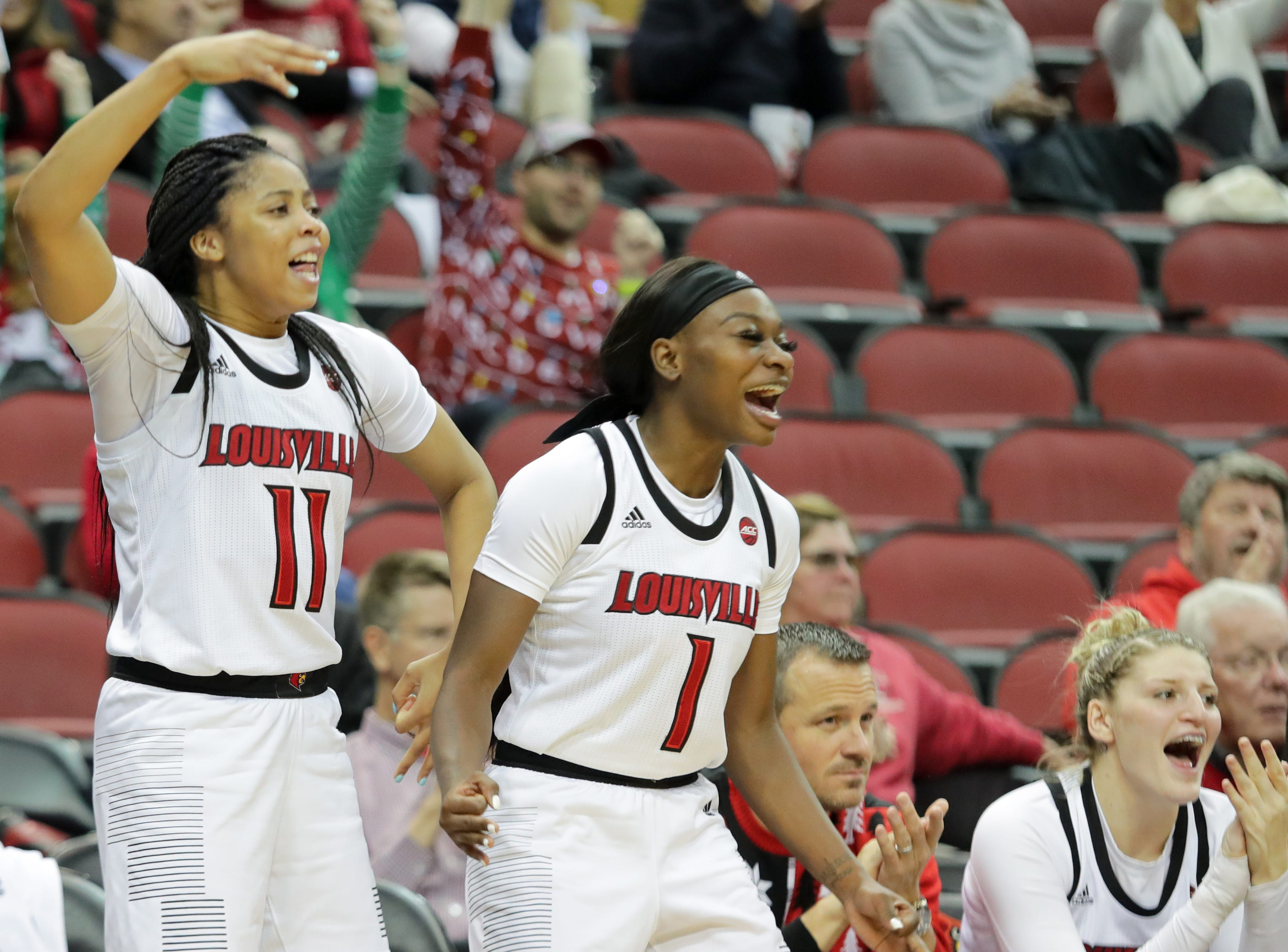 Louisville's Dana Evans (#1) and Arica Carter celebrate from the bench.  