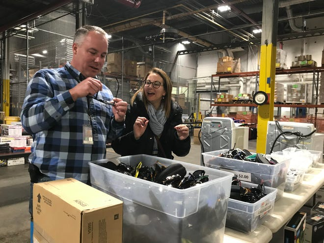 Ron Turner, program supervisor at the state of Michigan's Surplus Store, looks through a bucket of sunglasses with Christyn Herman on Wednesday, Dec. 5 at the West St. Joseph Street warehouse. The store will open for just the second time this year on Dec. 8.