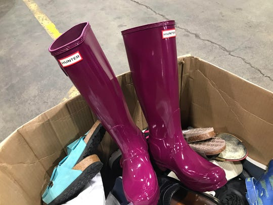 A pair of Hunter brand boots sits atop a box of shoes that will be sold during the state of Michigan's Surplus Store sale on Dec. 8.
