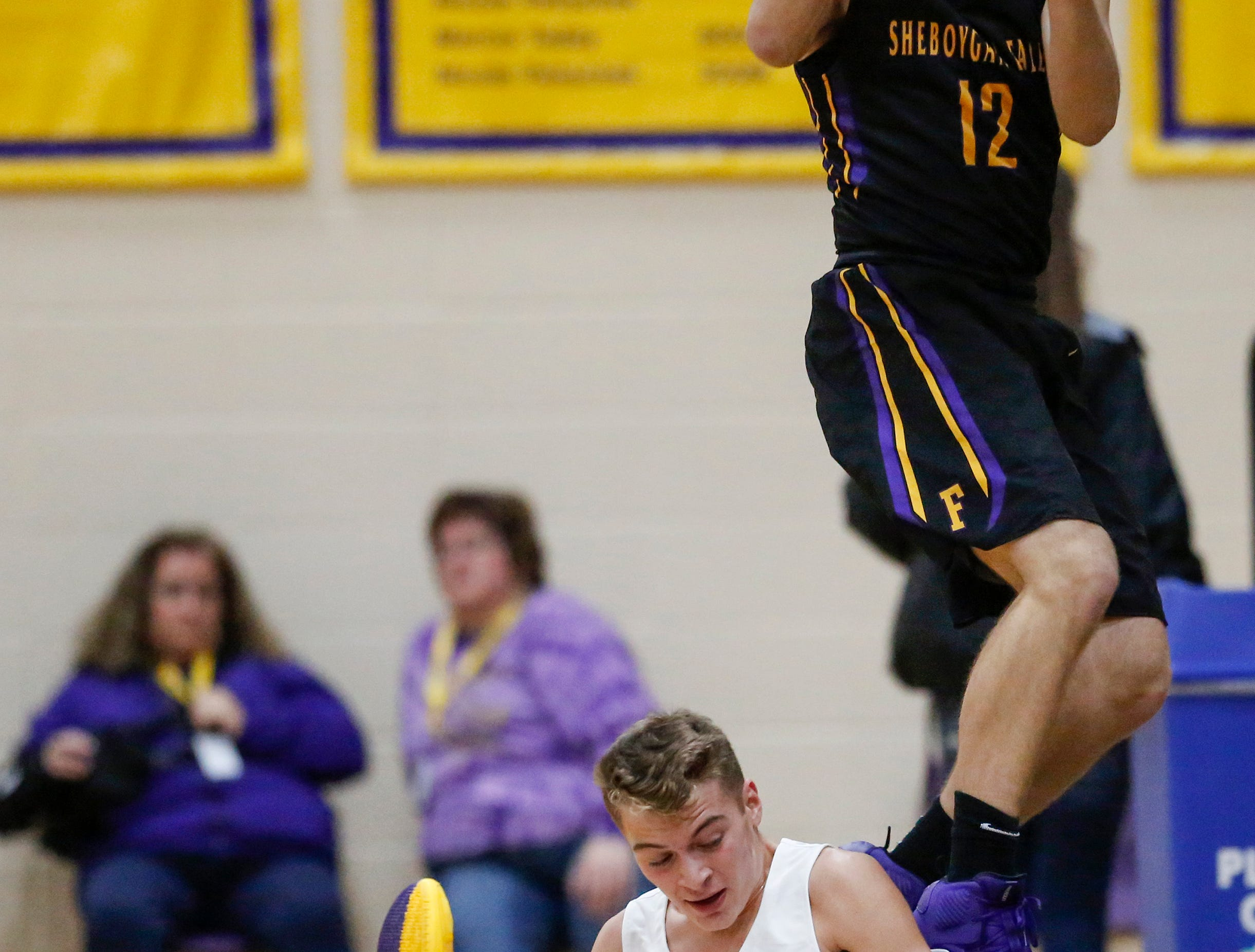 Sheboygan Falls' Langdon Thiel leaps over Two Rivers' Alexander Klein for a loose ball during an Eastern Wisconsin Conference game at Two Rivers High School Tuesday, December 4, 2018, in Two Rivers, Wis. Joshua Clark/USA TODAY NETWORK-Wisconsin