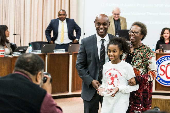 Dorsey Hopson poses for a photo with his daughter, Robbie Hopson, 11, and mother, Dorothy Hopson, during his last board meeting as Superintendent of the Shelby County Schools.