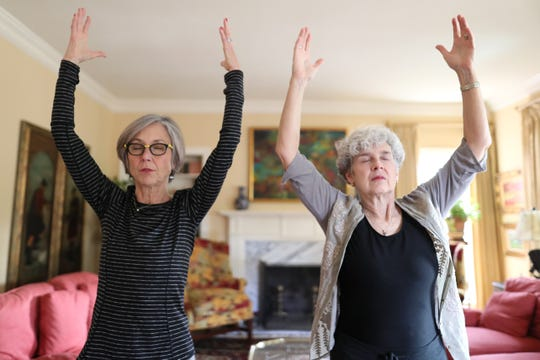 Sarla Nichols, left, instructs Mary McCalla in Qigong, a Chinese movement technique said to have healing properties, at Nichols' home on Tuesday, Dec. 4, 2018. Nichols, who was diagnosed with Stage 4 colon cancer earlier this year, has decided to invest her energy into re-opening a business she started nearly 20 years ago: Cooper Street Yoga.