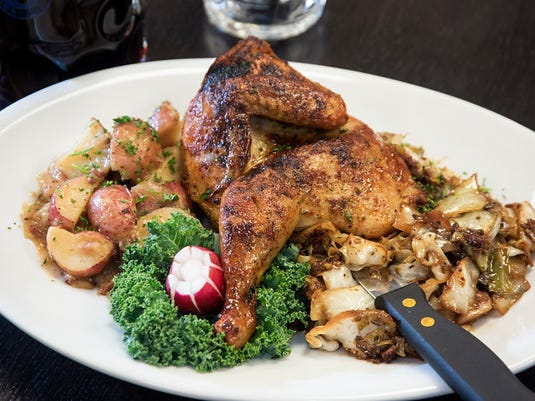 The Grill Hendl is a slow-roasted half chicken served with German potato salad and fried cabbage.