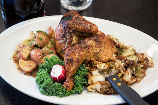 The Grill Hendl is a slow-roasted half-chicken served with German potato salad and fried cabbage.