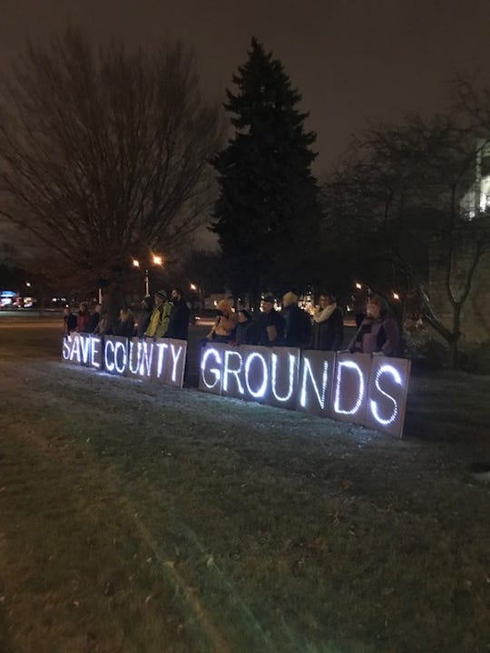 """A large group of passionate residents stand outside of the Wauwatosa Public Library on Dec. 4. Each person held up lit up letters which spelled out """"Save County Grounds."""""""