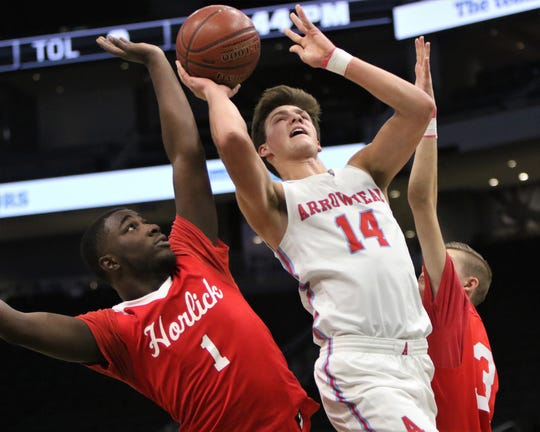 Arrowhead guard Carter Gilmore goes up for a shot between a pair of Racine Horlick defenders during a game last season. Gilmore officially committed to Wisconsin on Wednesday, the first day of the fall signing period.