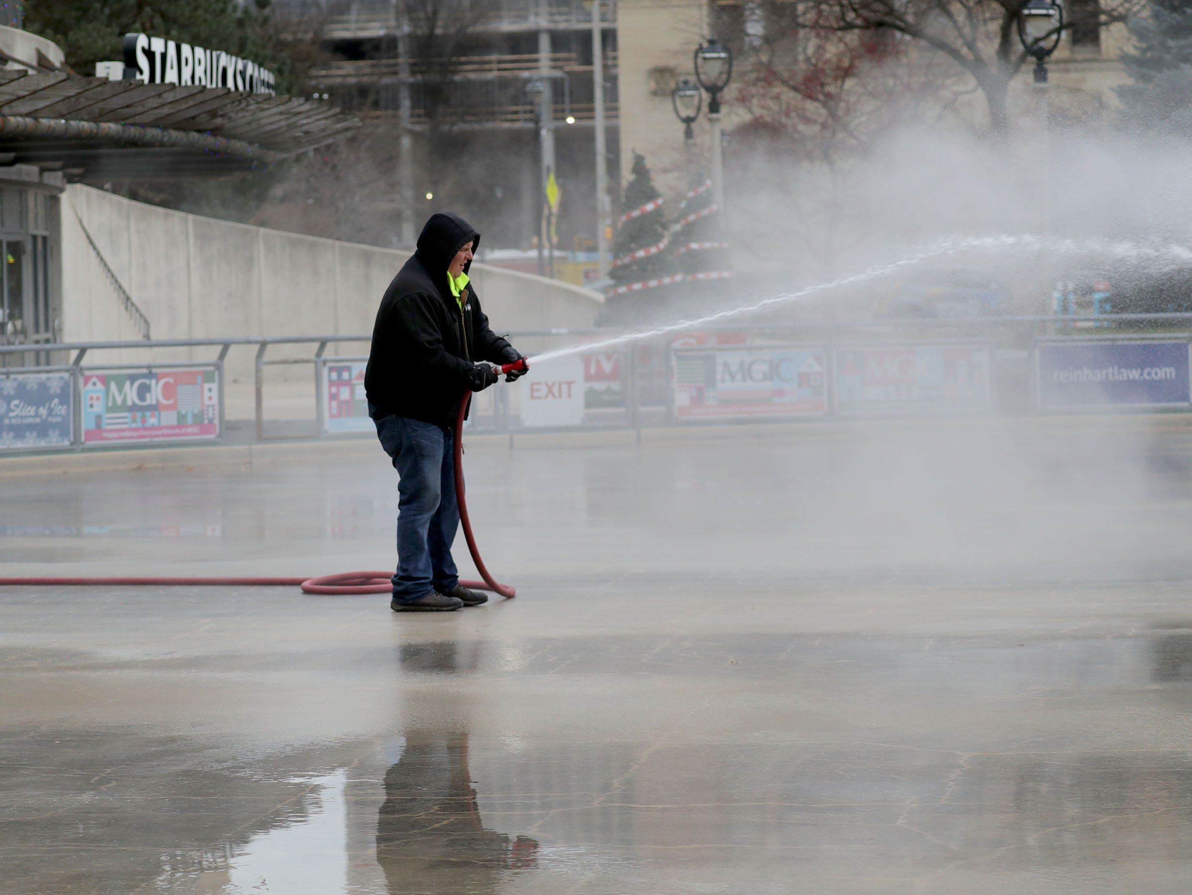 Patrick Vitrano with the Milwaukee County Parks sprays water on the Red Arrow ice rink on Wednesday. The rink usually opens in mid-December.