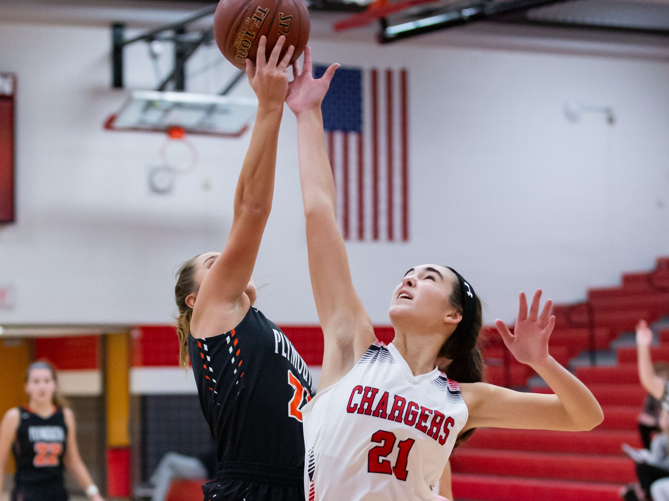 Hamilton senior Julia Nolde (right) steals a rebound from Plymouth's Gabi Mella during the game at Hamilton on Tuesday, Dec. 4, 2018.