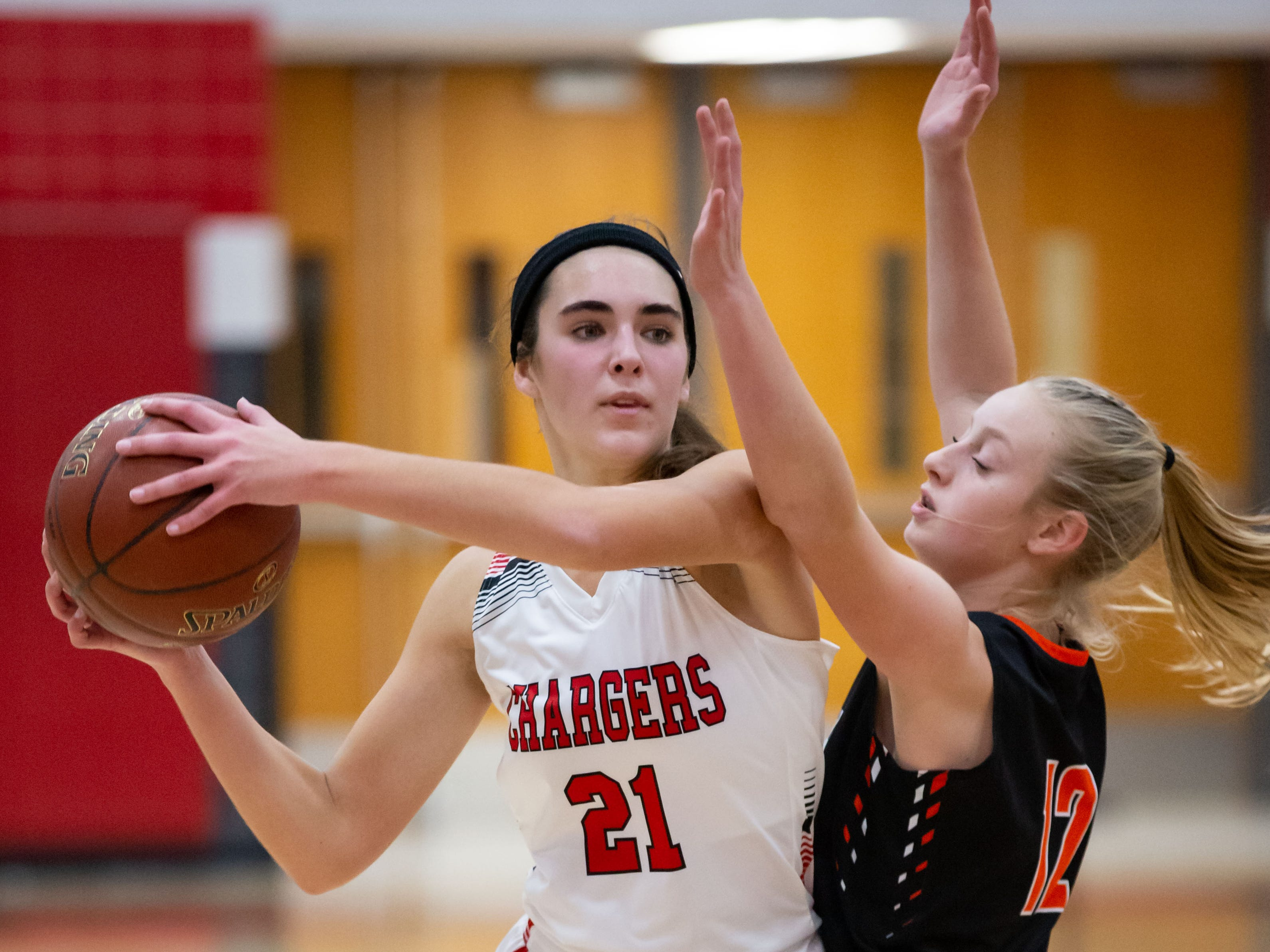 Hamilton senior Julia Nolde (21) looks to get around Plymouth's Ava Booth (12) during the game at Hamilton on Tuesday, Dec. 4, 2018.