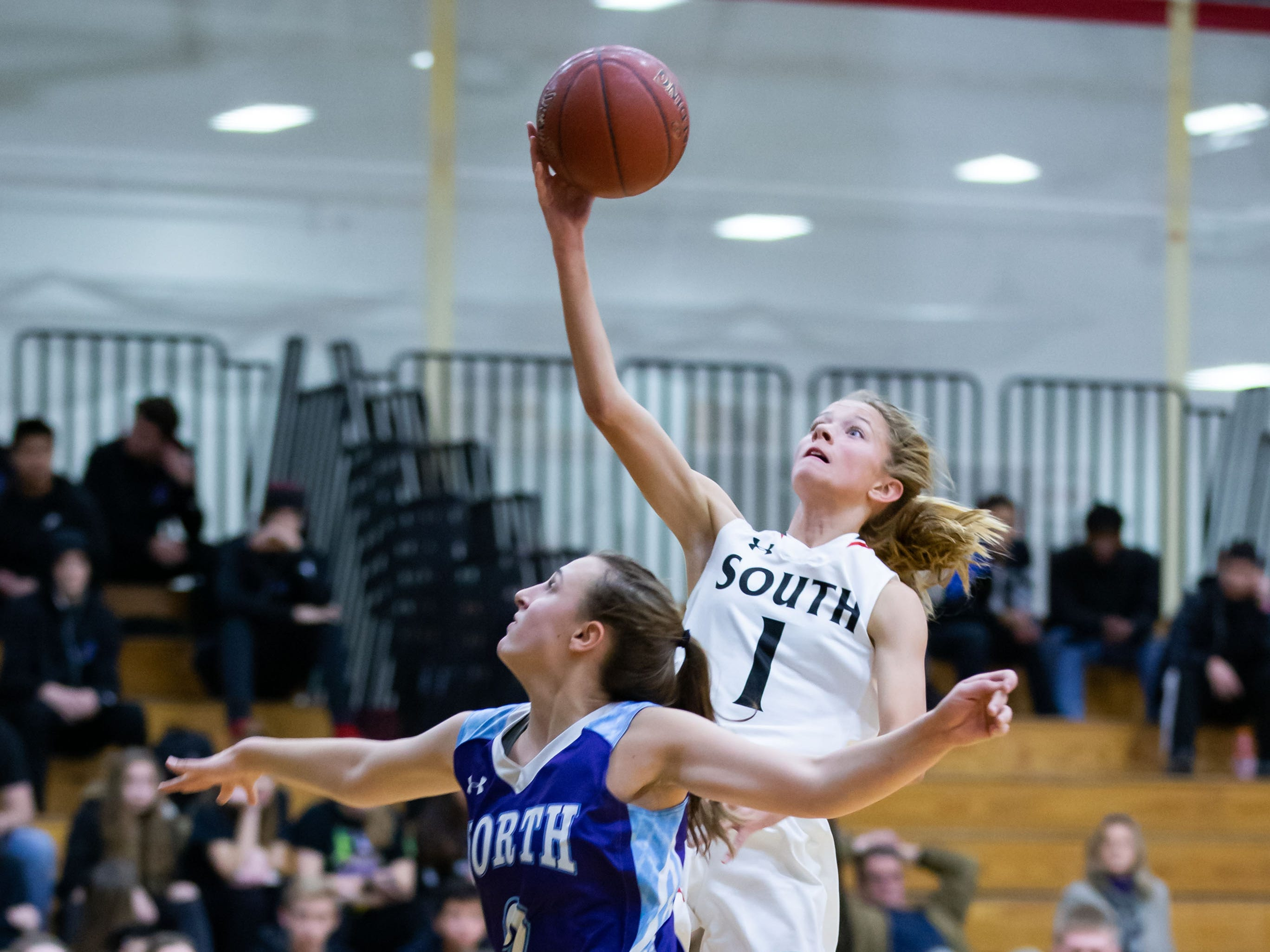 Waukesha South freshman Ashlyn Skinner-Barrett (1) drives in for a layup over Waukesha North's Olivia Osborn (2) at South on Tuesday, Dec. 4, 2018.