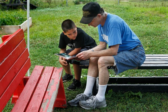 """Larry Hoffman reads """"Monster of the Deep"""" to Antonio Torres during the """"We Got This"""" reading program in the urban garden at N. 9th and W. Ring St."""