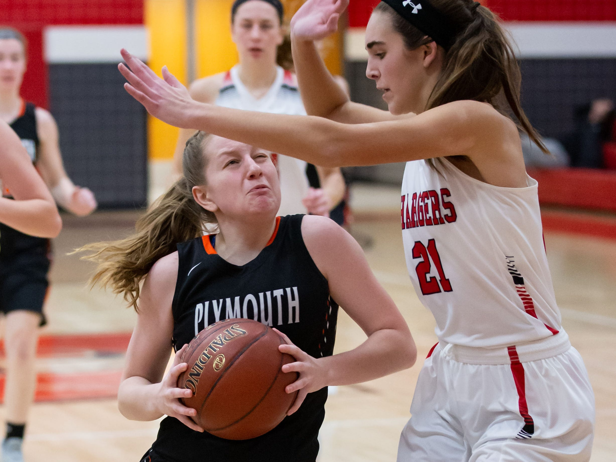 Plymouth junior Alesha Kaat-Fohr (4) battles Hamilton's Julia Nolde (21) in the lane at Hamilton on Tuesday, Dec. 4, 2018.