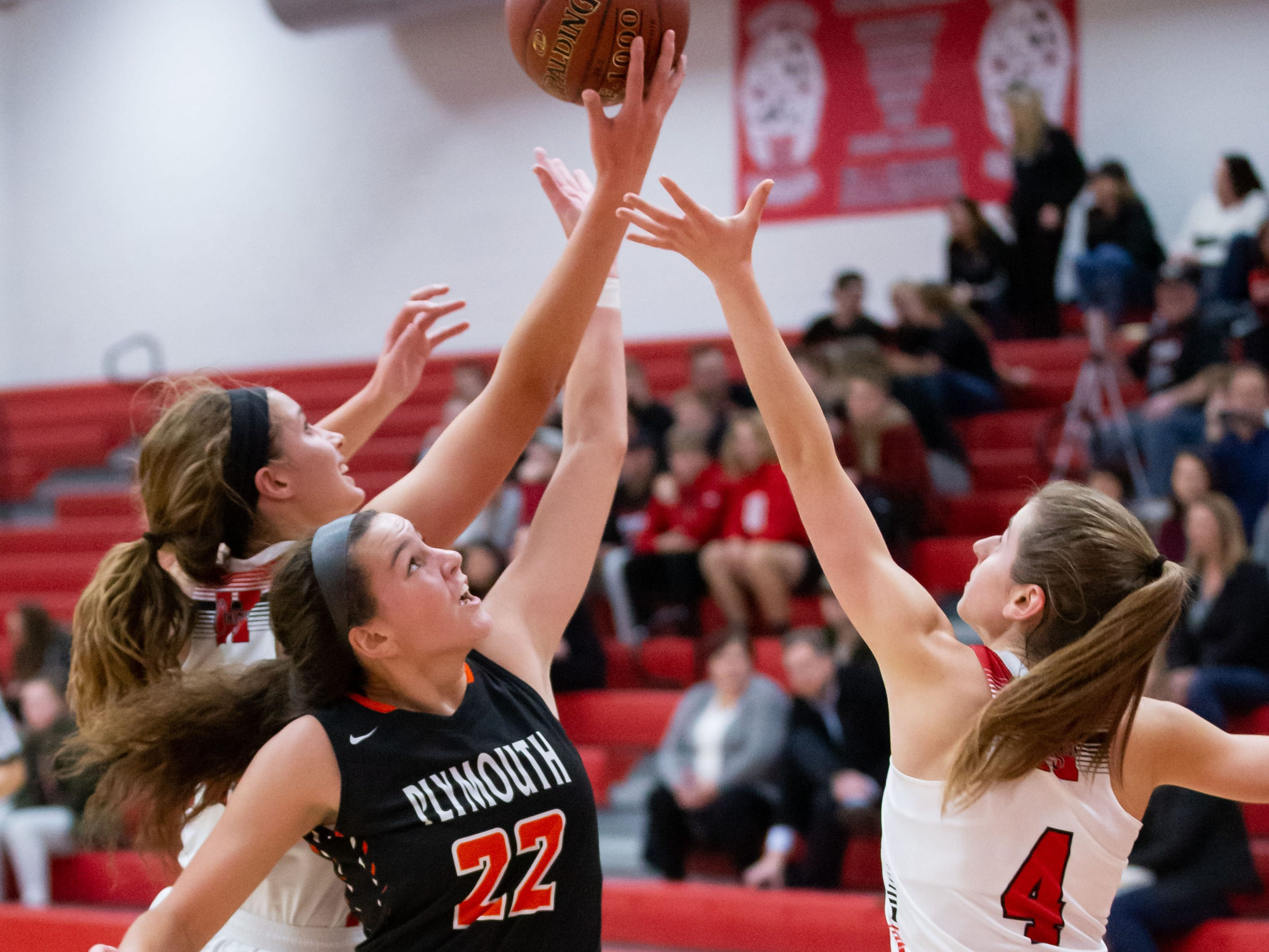 Hamilton junior Lexi Konop (left) and Kate Fantl (4) battle for a rebound with Plymouth's Kalani Smith (22) during the game at Hamilton on Tuesday, Dec. 4, 2018.