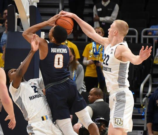 Marquette forward Joey Hauser blocks the shot of UTEP guard Jordan Lathon while Marquette guard/forward Sacar Anim draws a charge.