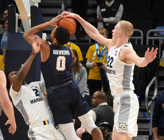 Marquette forward Joey Hauser blocks the shot of UTEP guard Jordan Lathon while Marquette guard/forward Sacar Anim draws a charge.