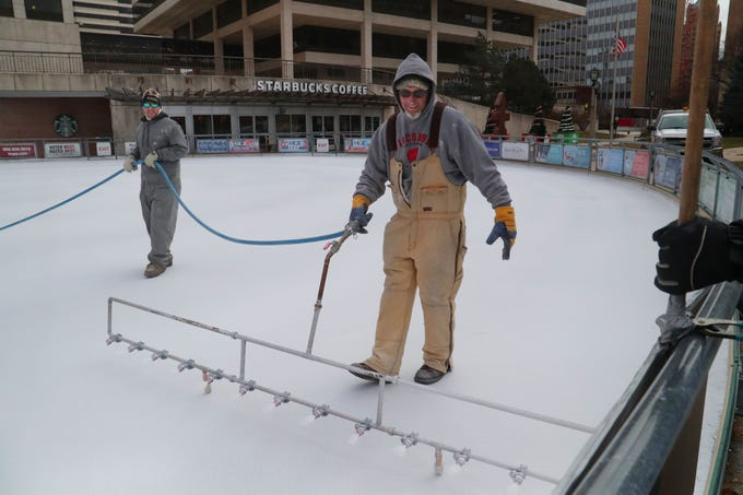 Tim Hanson (right), a painting supervisor with the Milwaukee County Parks and Jake Marsch with the Milwaukee County Parks uses a sprayer to paint the Red Arrow ice rink on Wednesday.  The Slice of Ice in Red Arrow Park ice rink is prepared by applying a special white ice paint that's applied on a thin layer of ice so that the sun doesn't melt the ice. The rink usually opens in mid-December.