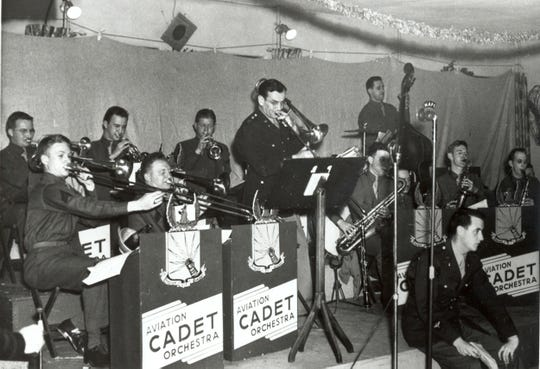 Captain Glenn Miller, center, plays his trombone as part of the Aviation Cadet Orchestra during a concert for the enlisted men and women at Maxwell Field, Alabama, on Christmas Eve, 1942.