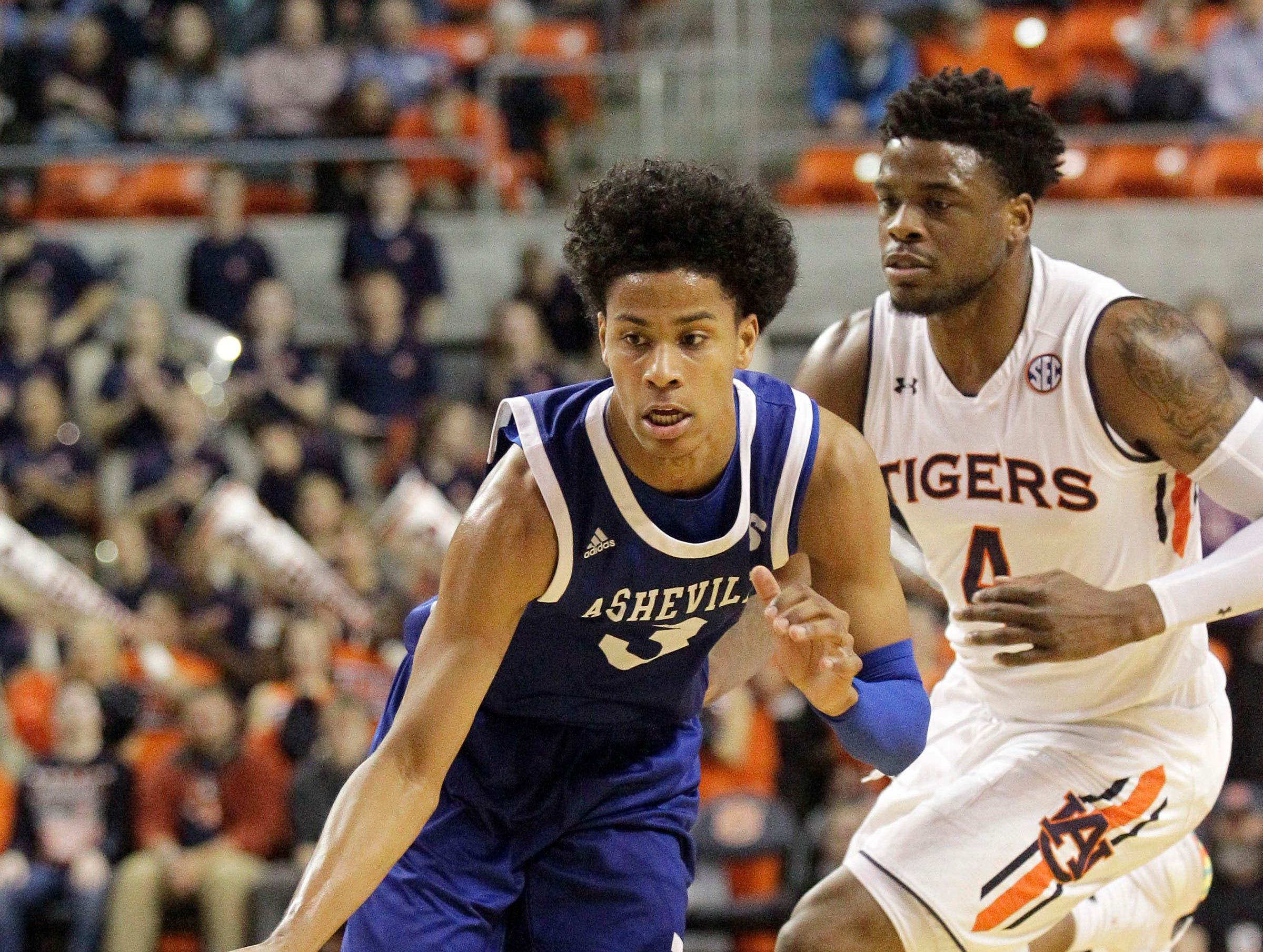 Dec 4, 2018; Auburn, AL, USA; UNC-Asheville Bulldogs guard Tajion Jones (3) dribbles past Auburn Tigers guard Malik Dunbar (4) during the first half at Auburn Arena. Mandatory Credit: John Reed-USA TODAY Sports
