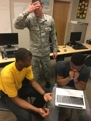 From left, Rasul Lee, Senior Airman Scott Mitchell and JaTavian Lusane work on a project for a tech competition at Carver High School.