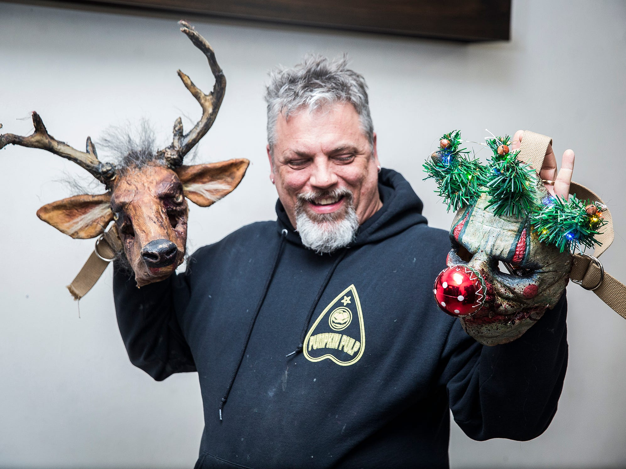 Brian Blair holds Christmas-themed horror masks at Cornerstone which will be the home of the Christmas Scarol haunted house on Dec. 15.