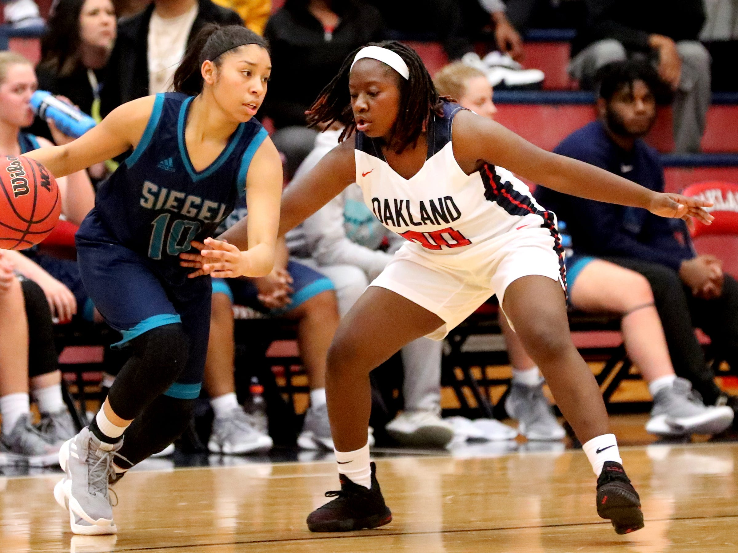 Siegel's Monica Peralta (10) moves the ball around the court as Oakland's Terianna Covington (00) guards her during the game at Oakland on Tuesday, Dec.. 4, 2018.