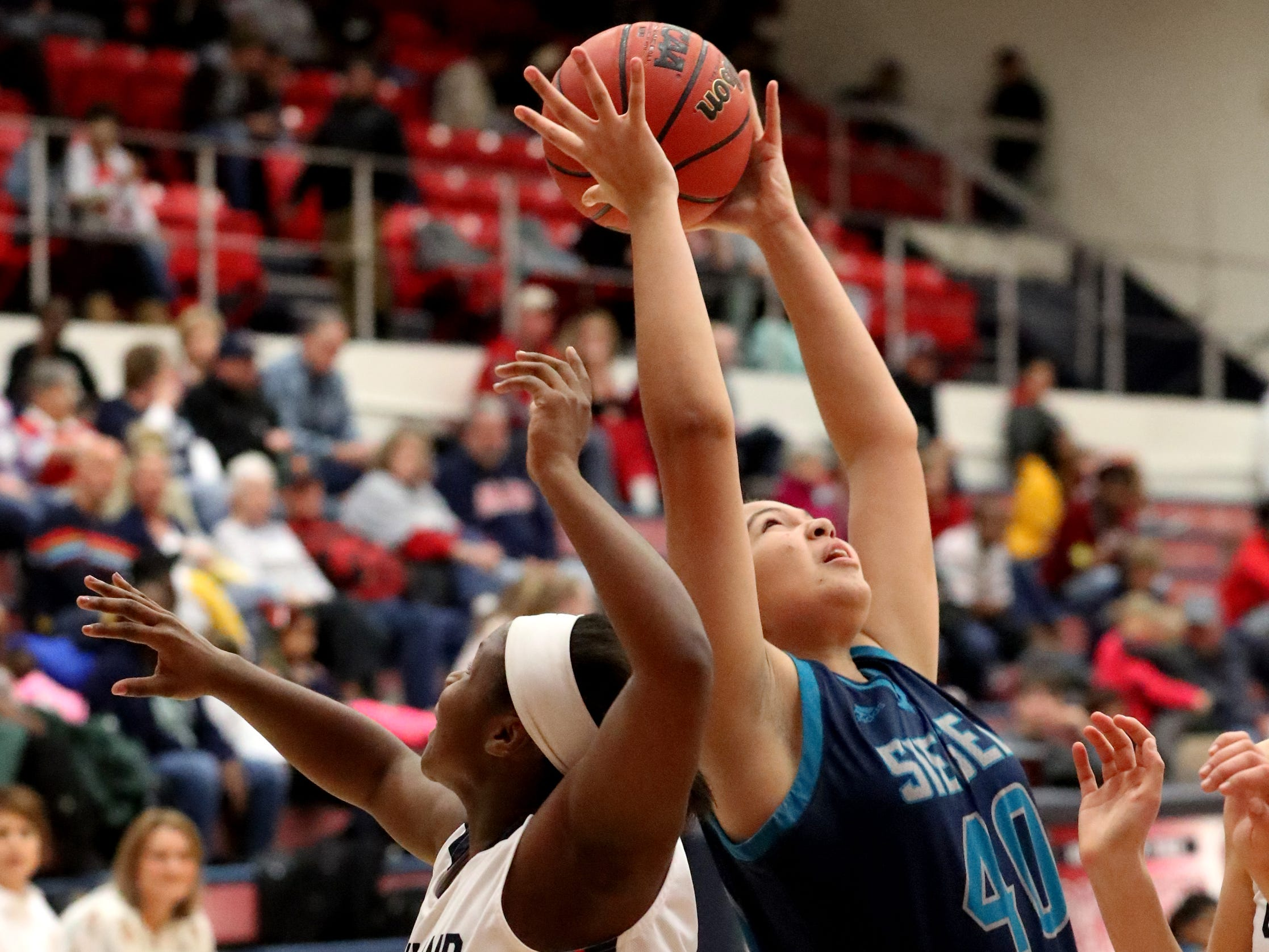 Siegel's Genesis Sneed (40) grabs a rebound as Oakland's Erykah Collier (32) also goes for the ball during the game at Oakland on Tuesday, Dec.. 4, 2018.