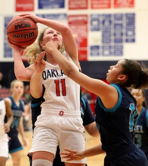 Oakland's Claira McGowan (11) goes up for a basket as Siegel's Monica Peralta (10) guards her during the game at Oakland on Tuesday, Dec.. 4, 2018.