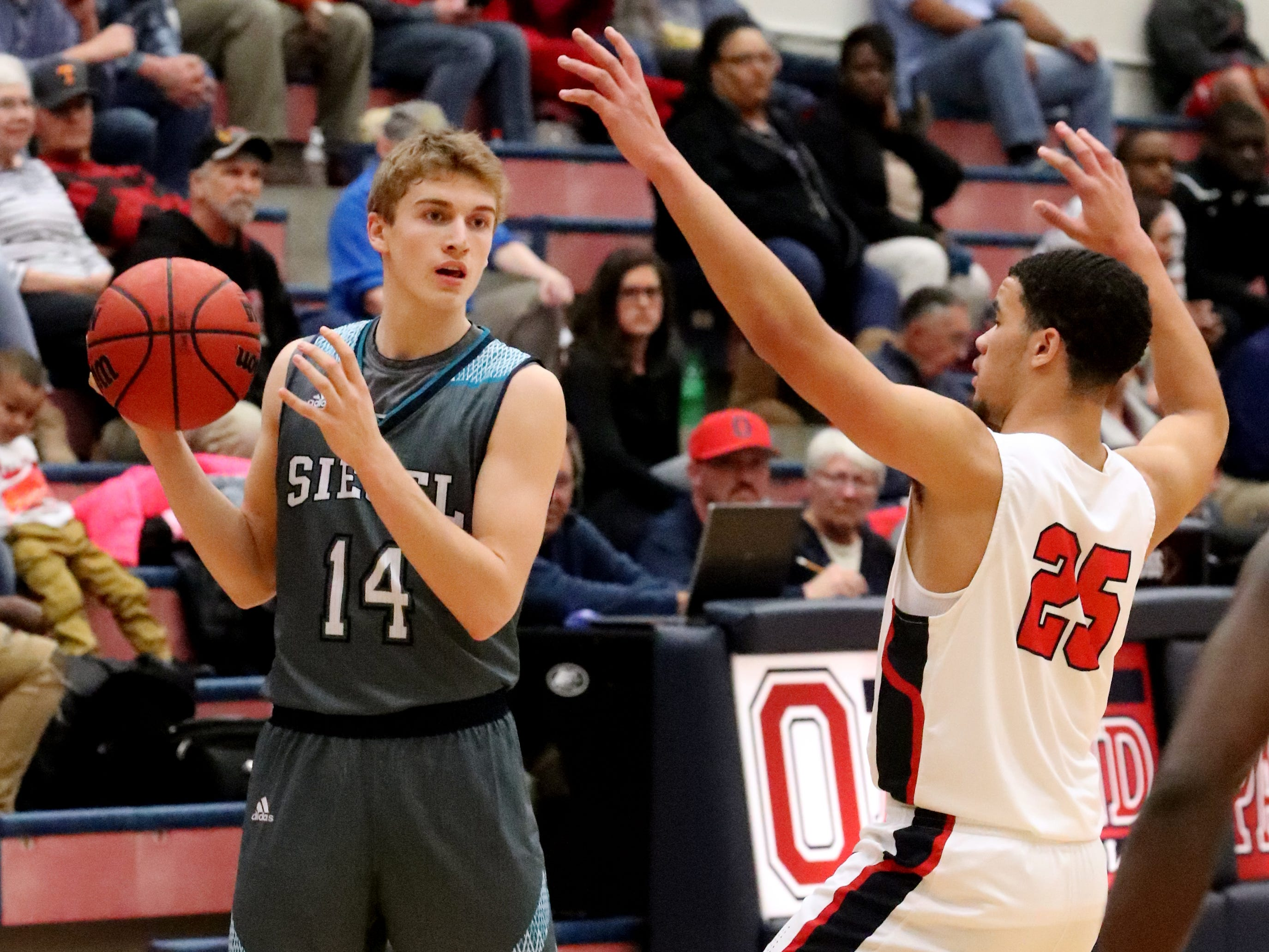 Siegel's Matthew Schneider (14) looks for a player to pass to as Oakland's Lamarius Jackson (25) guards him on Tuesday, Dec.. 4, 2018.