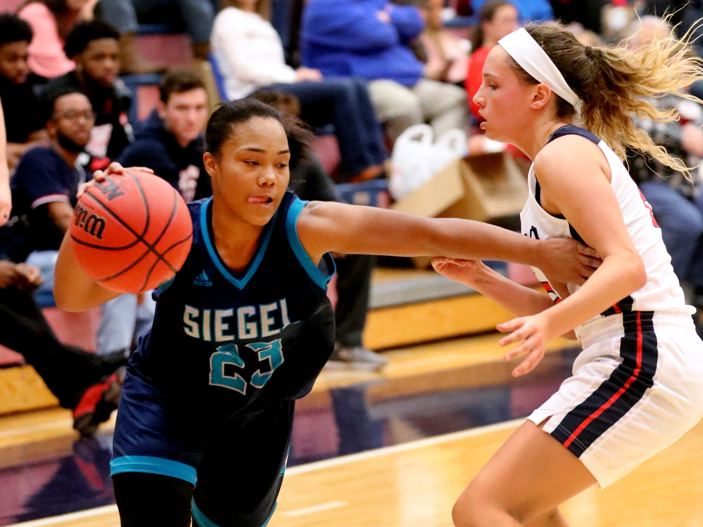 Siegel's Serenity Lillard (23) pushes around Oakland's Faith Adams (2) to head to the basket on Tuesday, Dec.. 4, 2018.