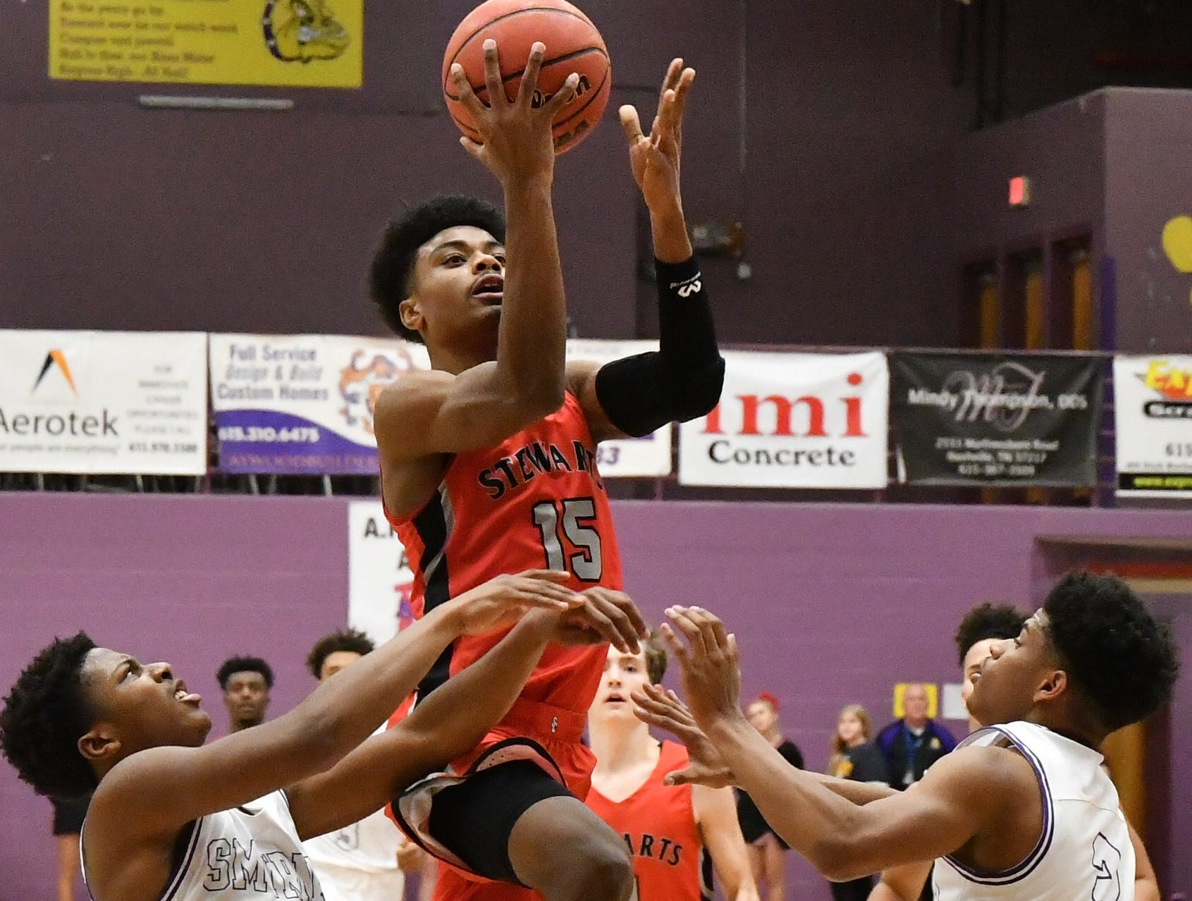 Stewarts Creek's Javontay Rollings goes up for a layup as Smyrna's Xavier Carter (11) and Tyler Lansden defend.