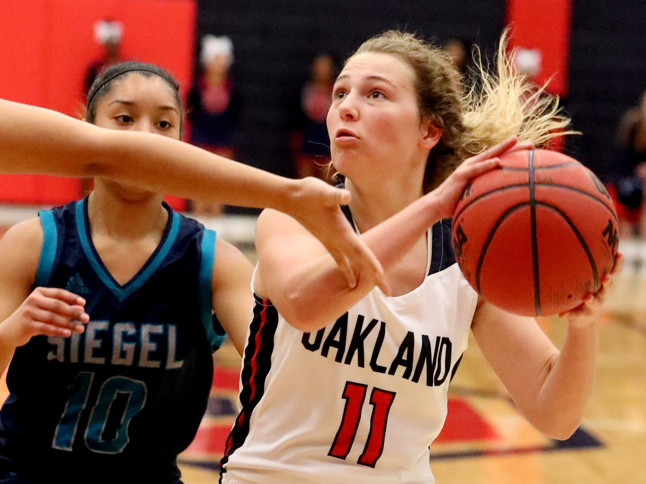 Oakland's Claira McGowan (11) goes up for a basket as Siegel's Genesis Sneed (40) guards her during the game at Oakland on Tuesday, Dec.. 4, 2018.