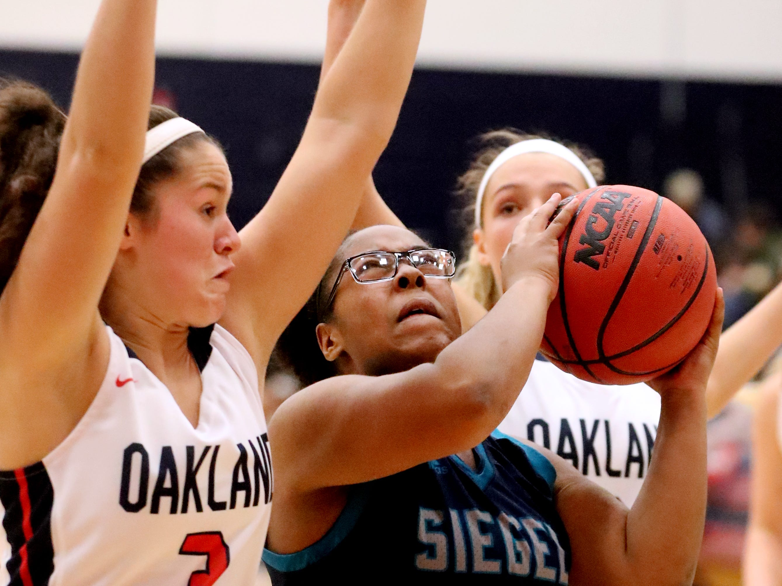 Siegel's Daisha Rankins (30) goes up for a basket as Oakland's Sydney Blankenship (3) and Faith Adams (2) guard her during the game at Oakland on Tuesday, Dec.. 4, 2018.