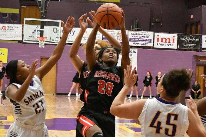 Stewarts Creek's Lauren Flowers drives in the lane as Smyrna's Jakila Wesley (21) and Chloe Wilder (45) defend Tuesday.