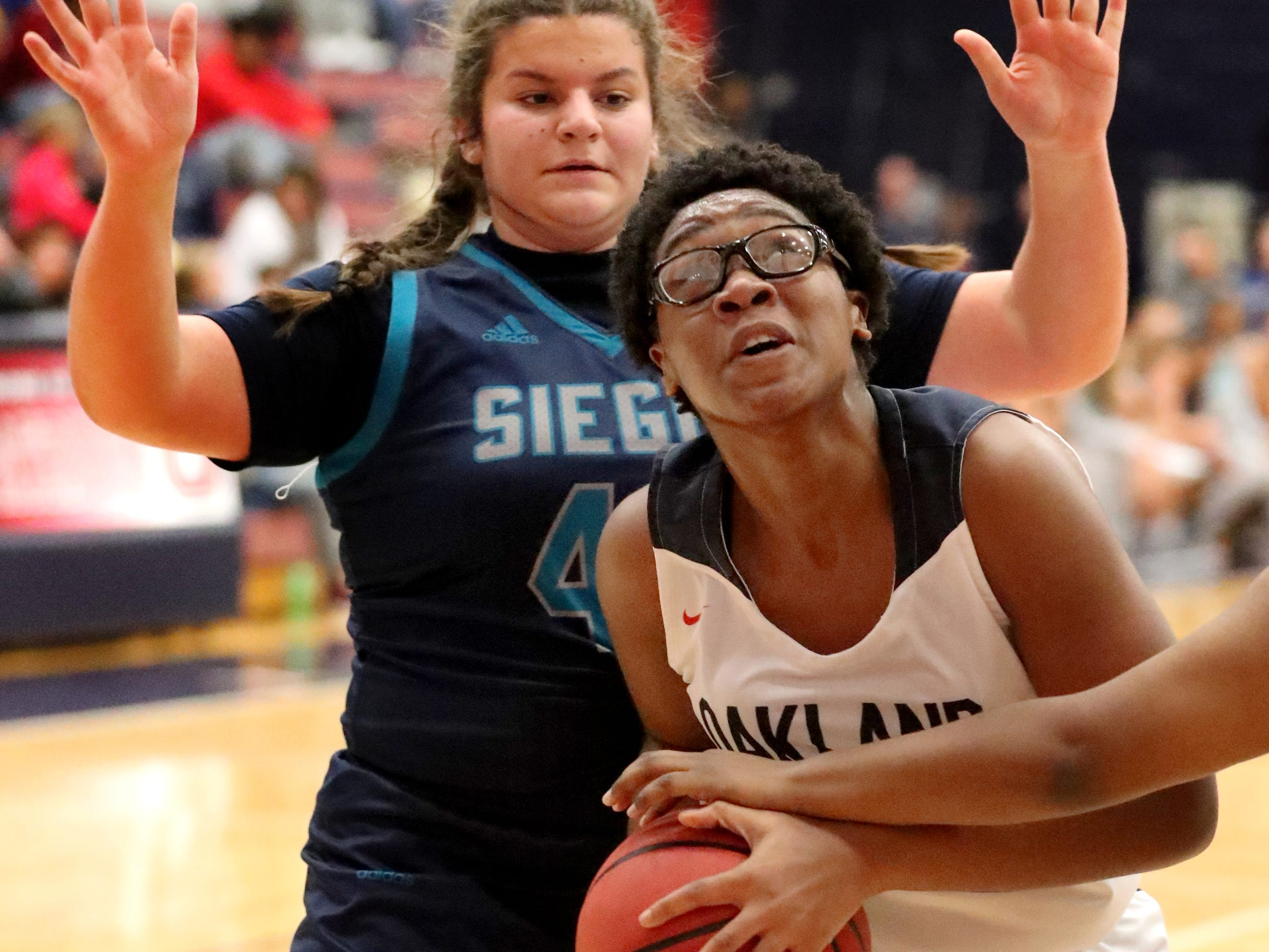 Oakland's Nicole Egeruoh (42) goes up for a shot as Siegel's Genesis Sneed (40) and Erin Vanhook (42) guard her during the game at Oakland on Tuesday, Dec.. 4, 2018.