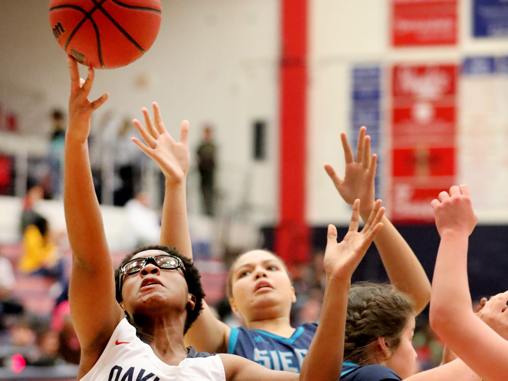 Oakland's Nicole Egeruoh (42) goes after a rebound as Siegel's Erin Vanhook (42) and Genesis Sneed (40) also fight for the rebound on Tuesday, Dec. 4, 2018.