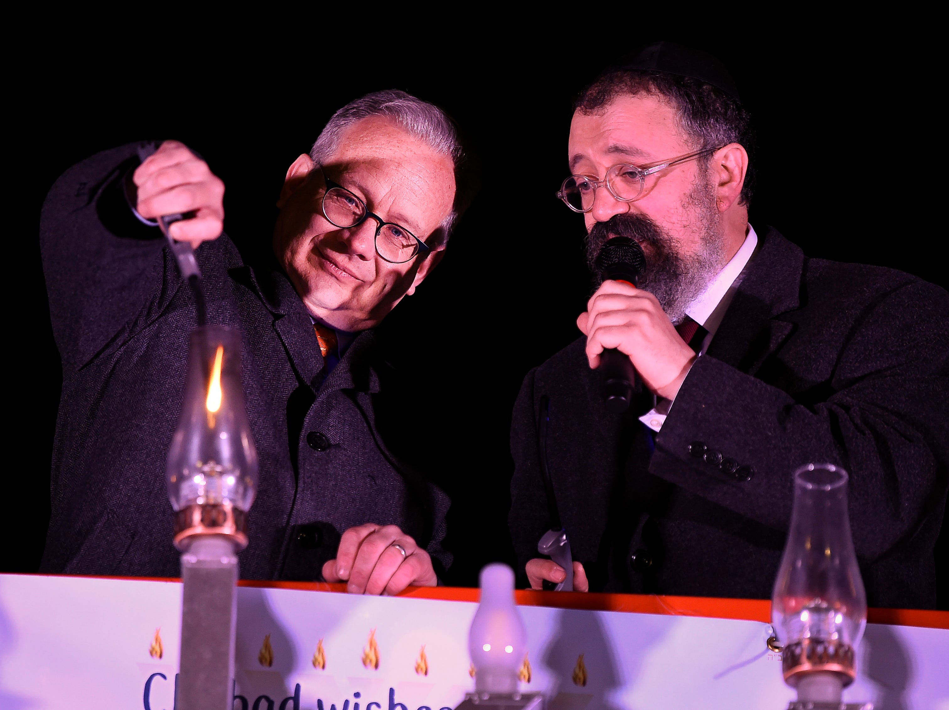 Mayor David Briley and Rabbi Yitzchok Tiechtel light candles during a Chanukah menorah lighting ceremony at Public Square Park Tuesday, Dec. 4, 2018, in Nashville, Tenn.