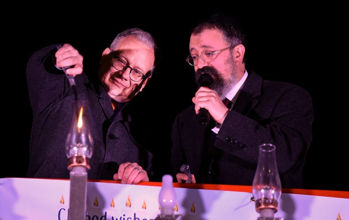 Mayor David Briley and Rabbi Yitzchok Tiechtel light candles during a Chanukah menorah lighting ceremony at Public Square Park Tuesday, Dec. 4, 2018, in Nashville, Tenn.