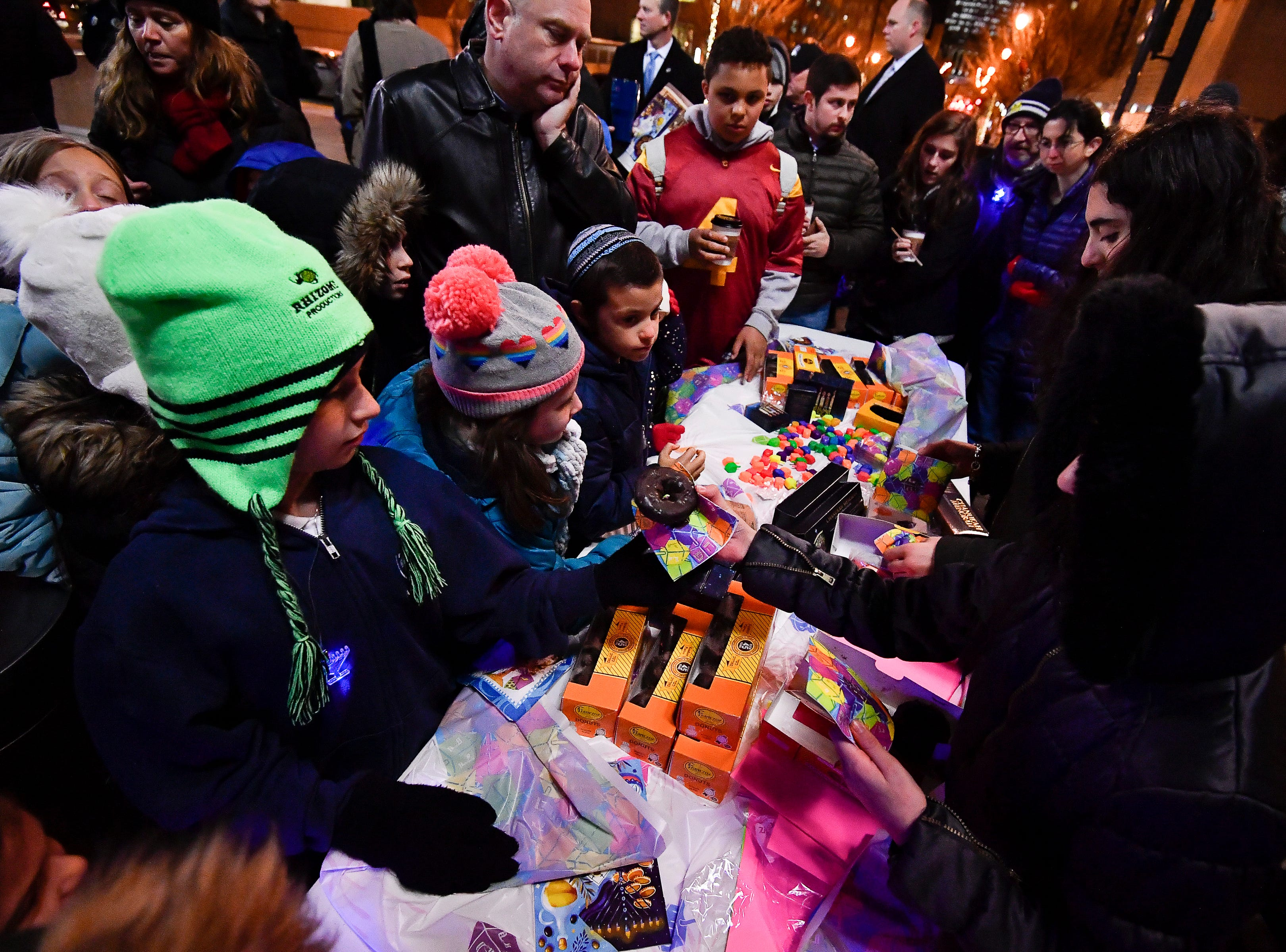Children enjoy special Chanuka Gelt and Donuts during a Chanukah menorah lighting ceremony at Public Square Park Tuesday, Dec. 4, 2018, in Nashville, Tenn.