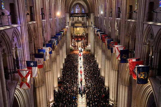 The casket of former President George H.W. Bush is carried down the aisle at Washington National Cathedral during his state funeral on Wednesday, Dec. 5, 2018.