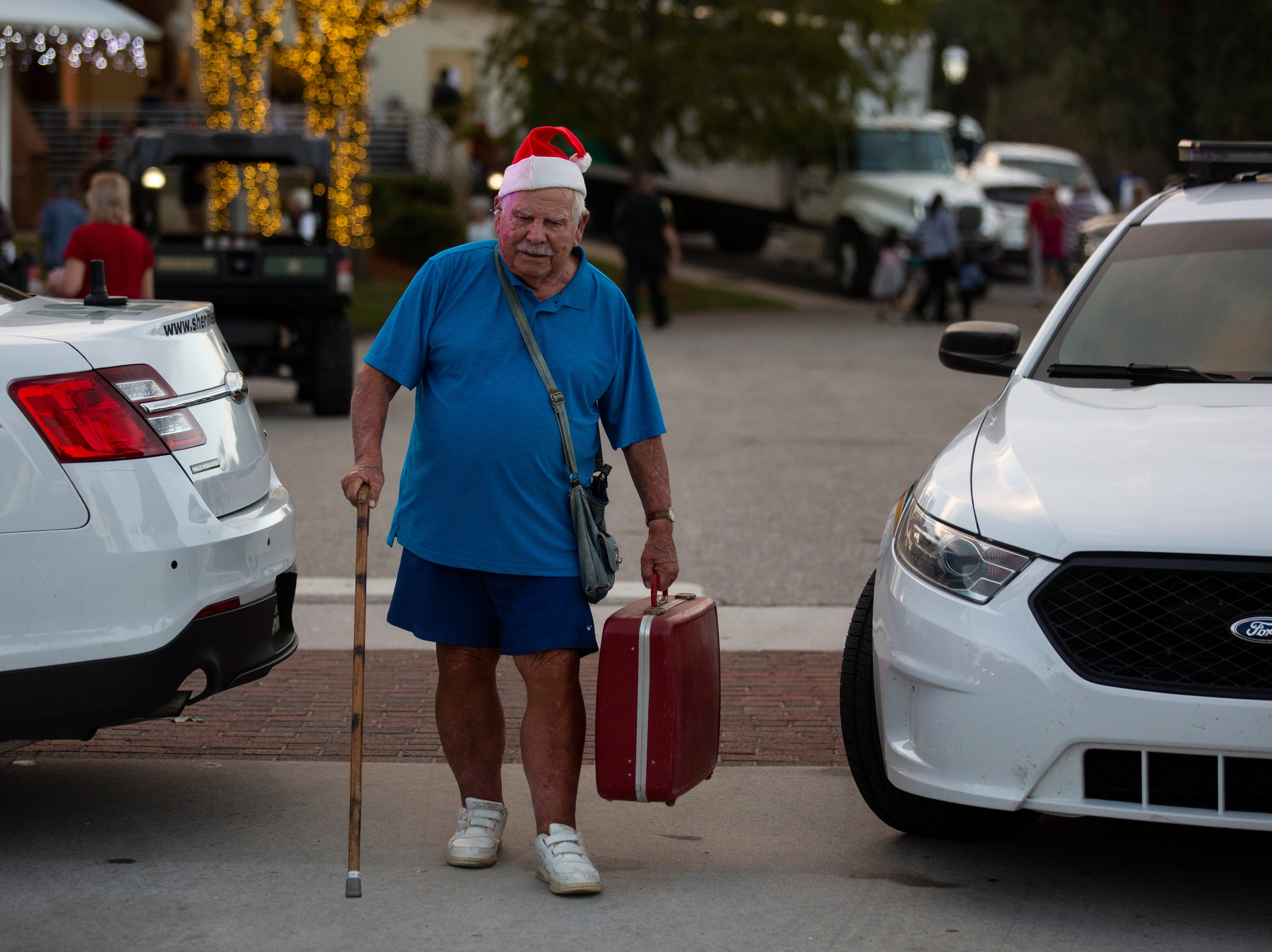 "Albert Dalton, 92, walks back to his car holding on to his accordion after performing Christmas tunes with the Bonita Village Band at the 19th annual Holiday in the Park on, Dec. 4, 2018 at the Riverside Park in Bonita Springs. Dalton was the founder of the band in 1991. ""I founded the band with seven people and now it has grown to 80,"" Dalton said."