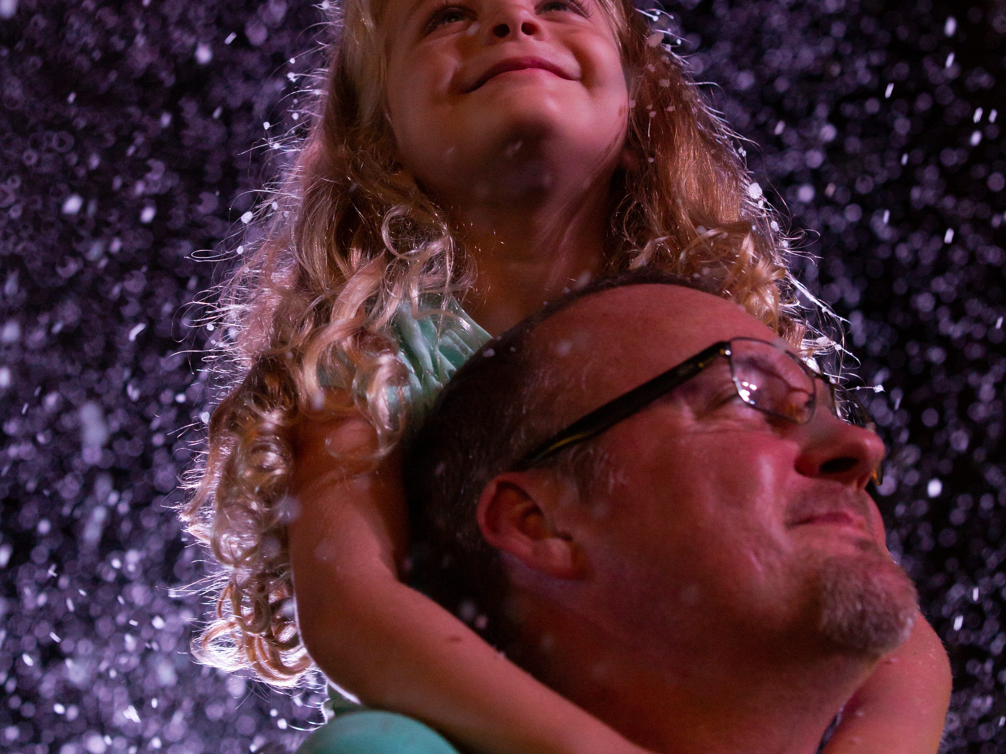 Four-year-old, Ashelynn Goins sits on her father, David Goins shoulder and enjoys faux winter blizzard during the 19th annual Holiday in the Park on Dec. 4, 2018 at the Riverside Park in Bonita Springs.