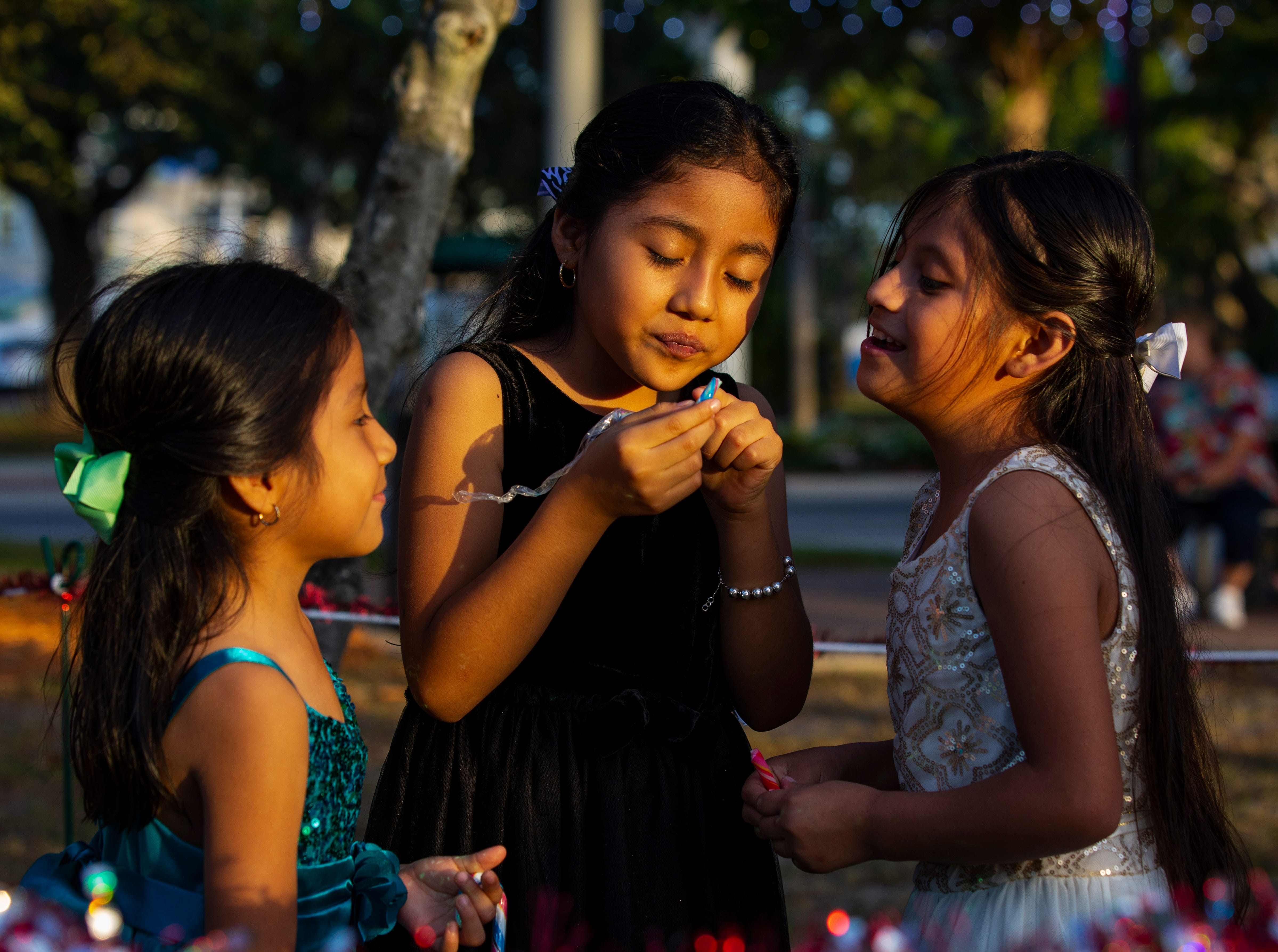 From the left, Alejandra Diaz, 5, Ellen Diaz, 8, and Maria Martin, 5, share a moment while waiting in line to meet Santa at Mrs. Claus during the 19th annual Holiday in the Park on Dec. 4, 2018 at the Riverside Park in Bonita Springs.