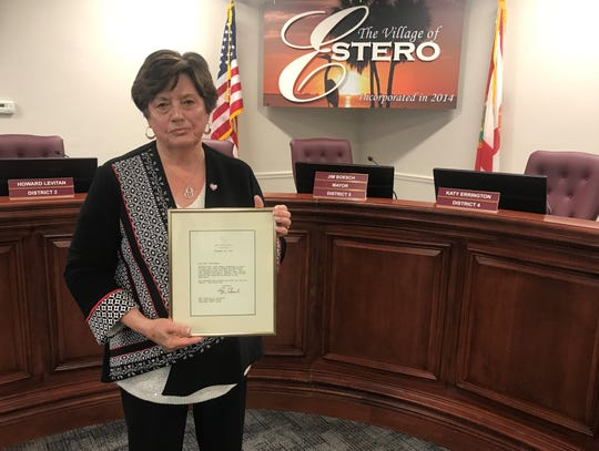 Estero Councilor Katy Errington stands in the village's council chambers with a letter former president George H.W. Bush wrote to her after her son, a sergeant in the U.S. Air Force, died in 1992.