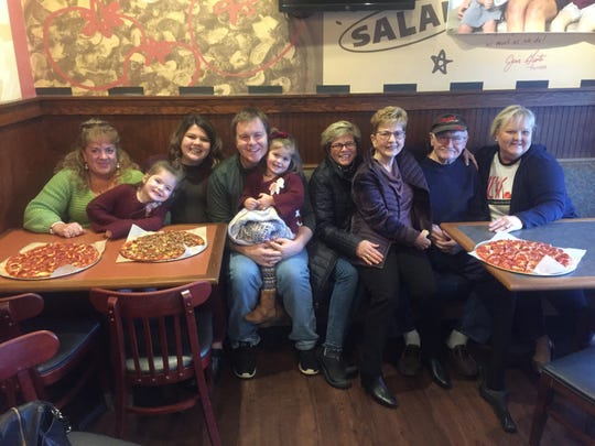 Maelée Leonard , center, with blankets on lap, gathers with family and friends before enjoying her Dec. 4 pizza party at the Pataskala Donatos.