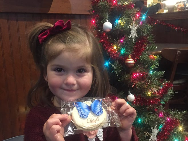 Maelée Leonard displays one of the special Cheryl's Cookies during her pizza party at the Pataskala Donatos on Dec. 4.