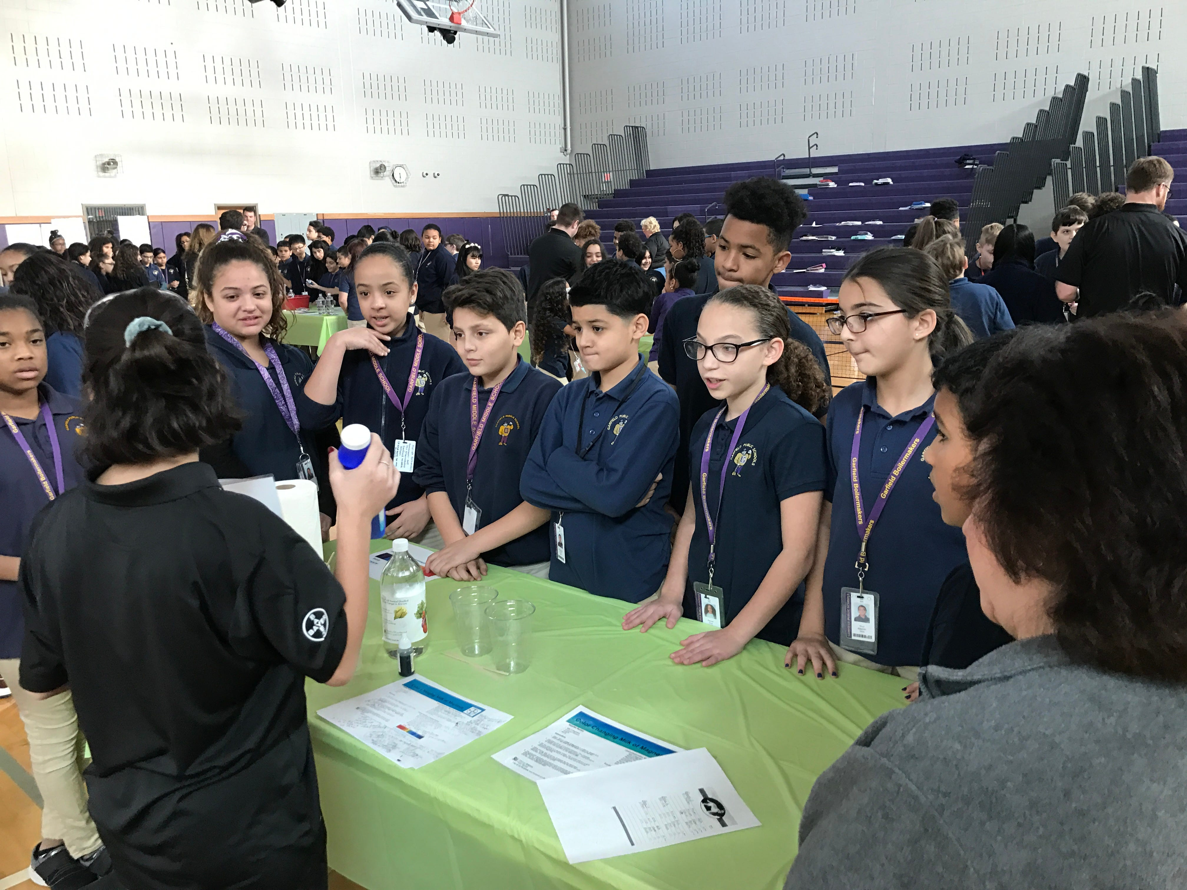 Garfield Middle School students learn about the acidity of household liquids during a visit from Bayer.